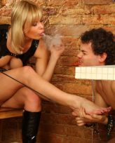Hot blonde babe likes to get her feet licked by her favorite foot stool slave