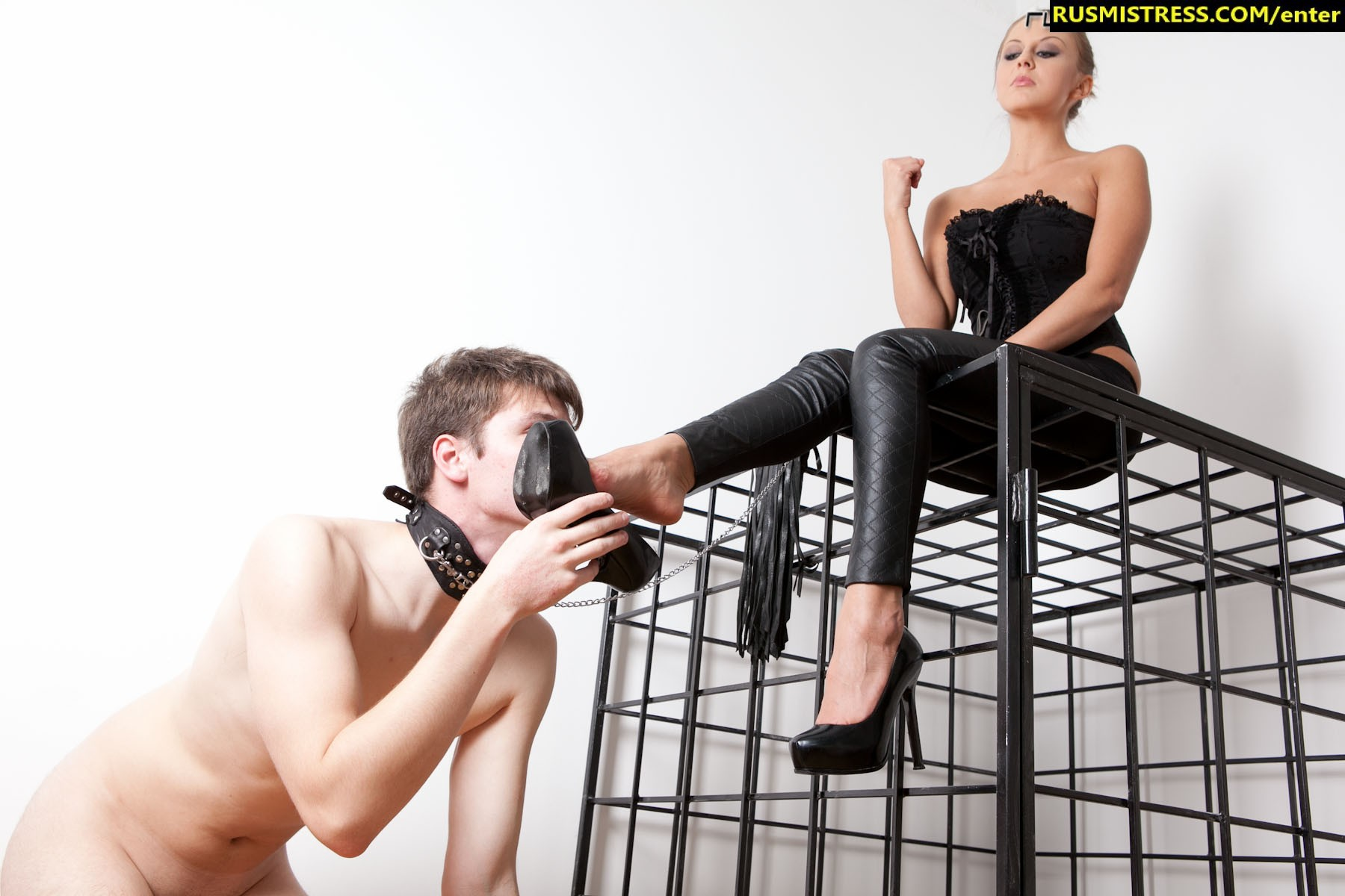 Slave is let out of his cage to get his mouth gagged with his domme's feet